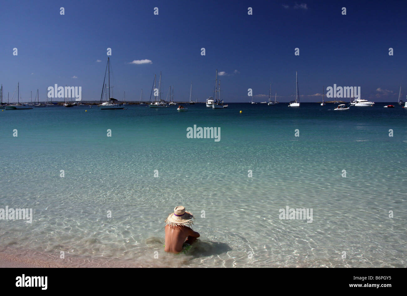 Young man with a straw hat sitting on the beach of Espalmador, in the Balearic Islands, looking at the horizon - Stock Image