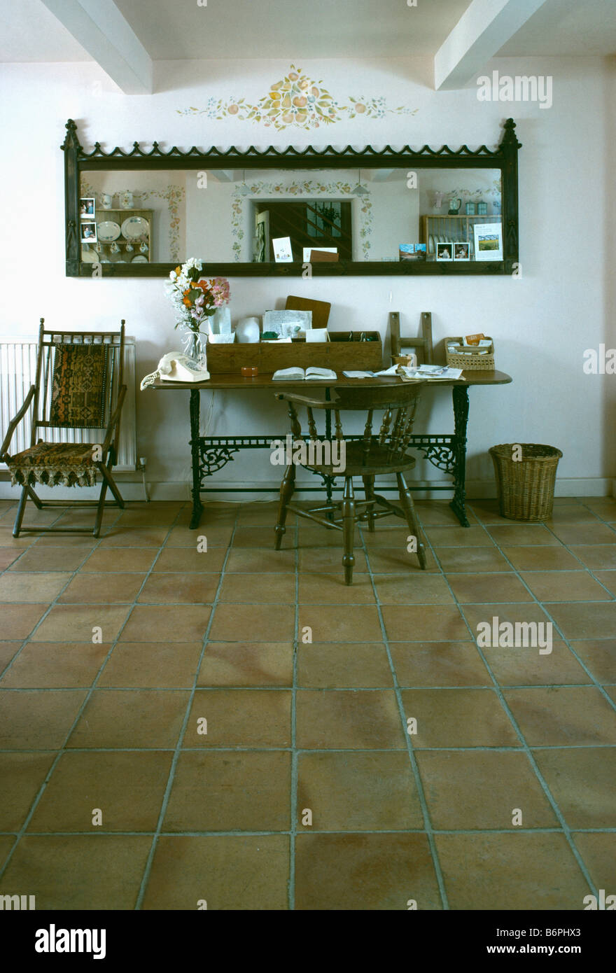 Antique terracotta floor tiles stock photos antique terracotta long narrow mirror above antique desk and chairs in study area of traditional white hall with dailygadgetfo Gallery