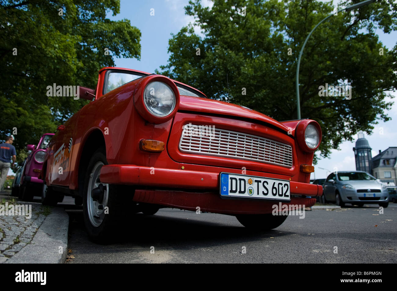 red soft top trabant parked badly on a west german side street - Stock Image