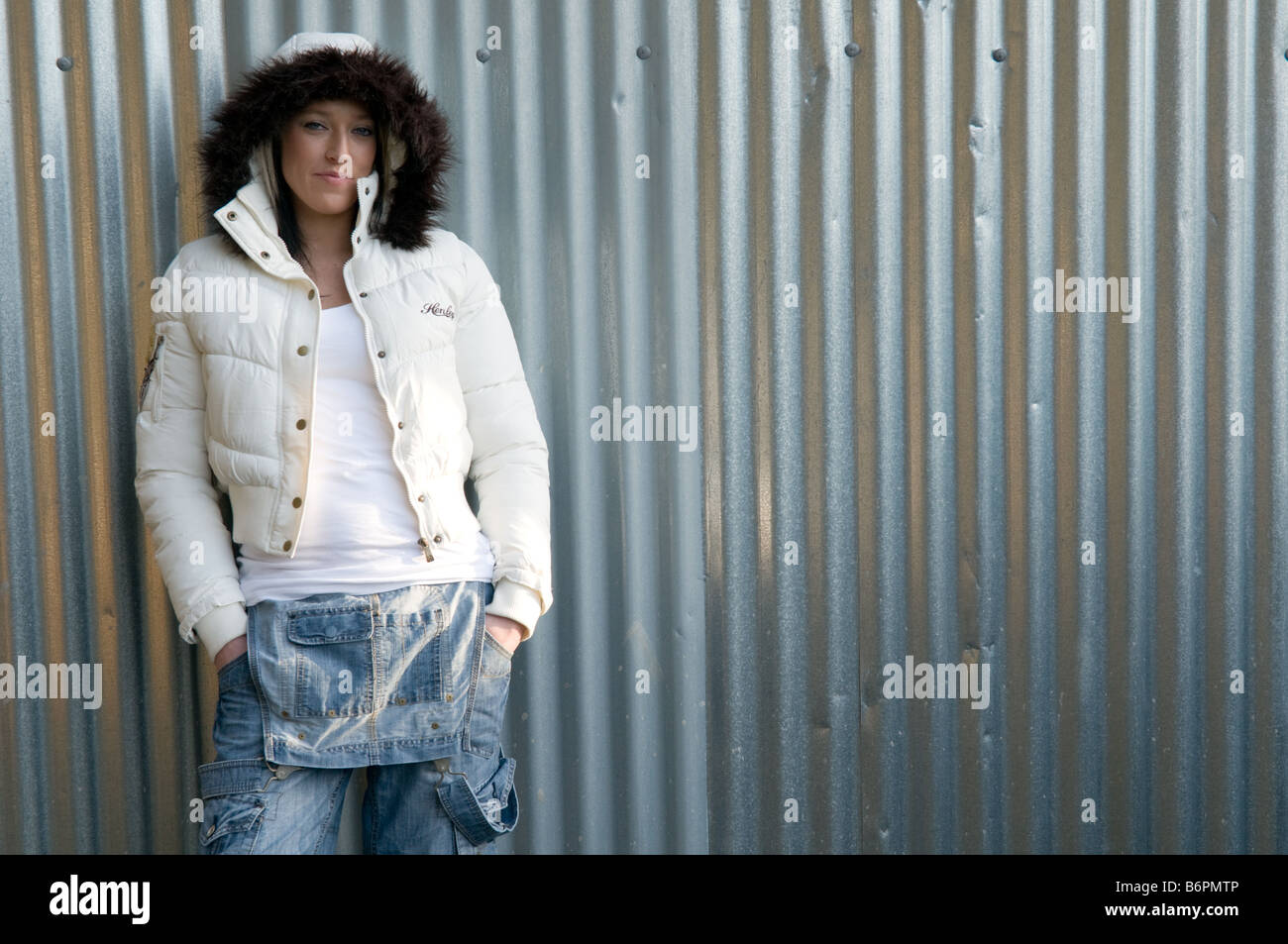 young smiling woman wearing a white fur trimmed jacket leaning on a corrugated iron metal wall - Stock Image
