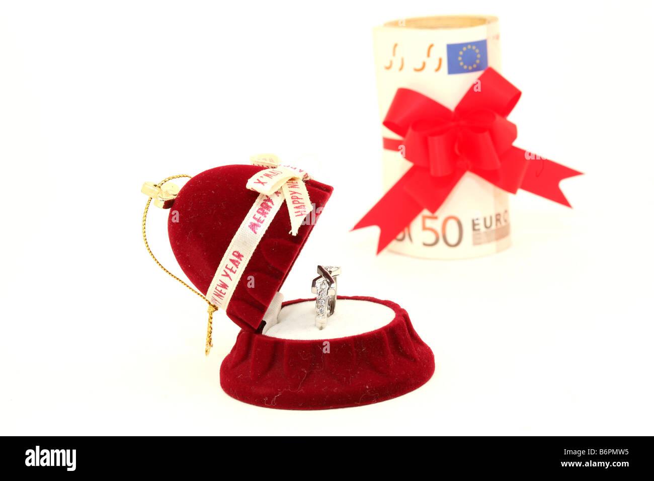 xmas gift box with white gold ring and euro money background isolated - Stock Image