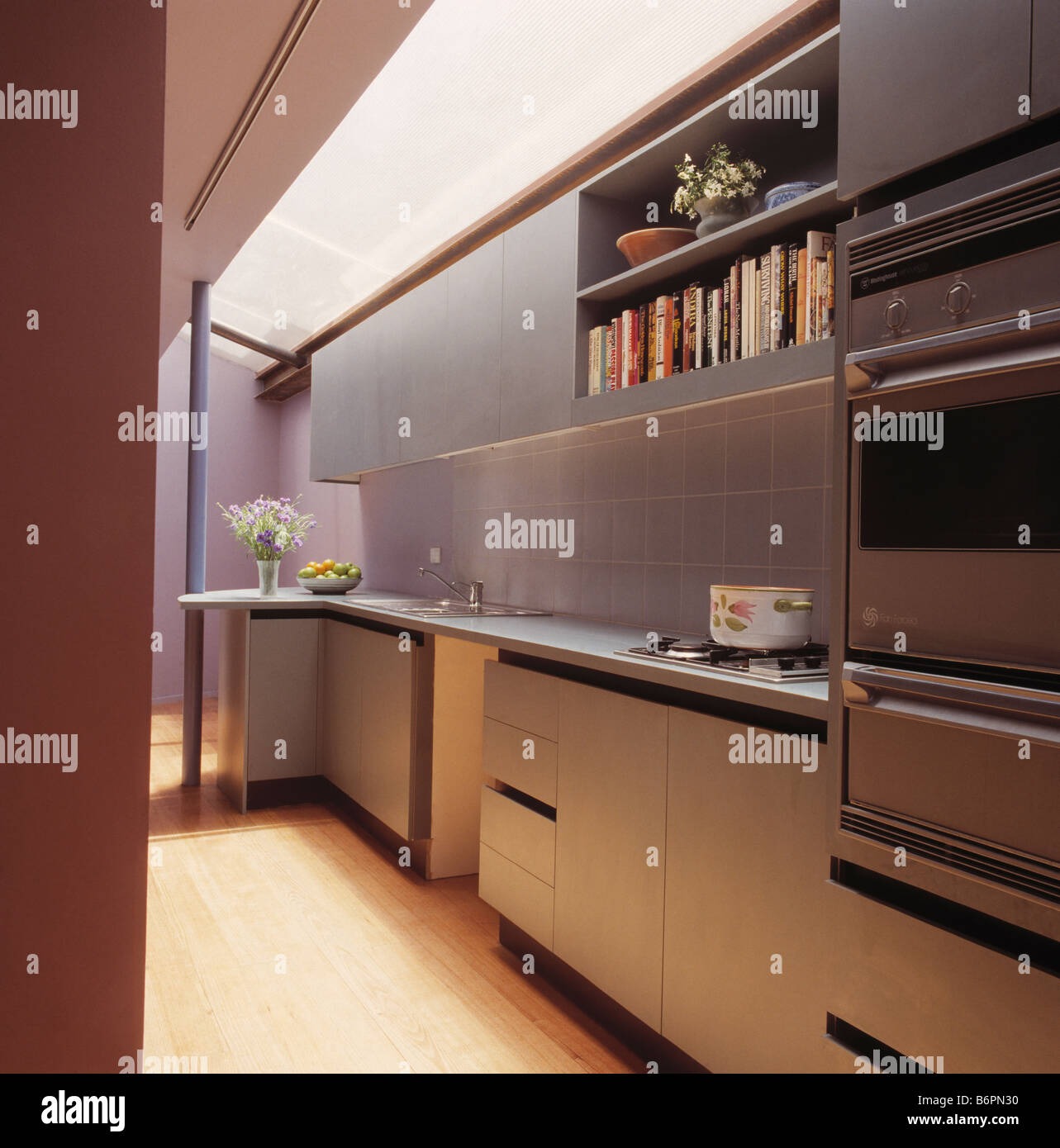 Modern galley kitchen with stainless steel splashback and grey units ...
