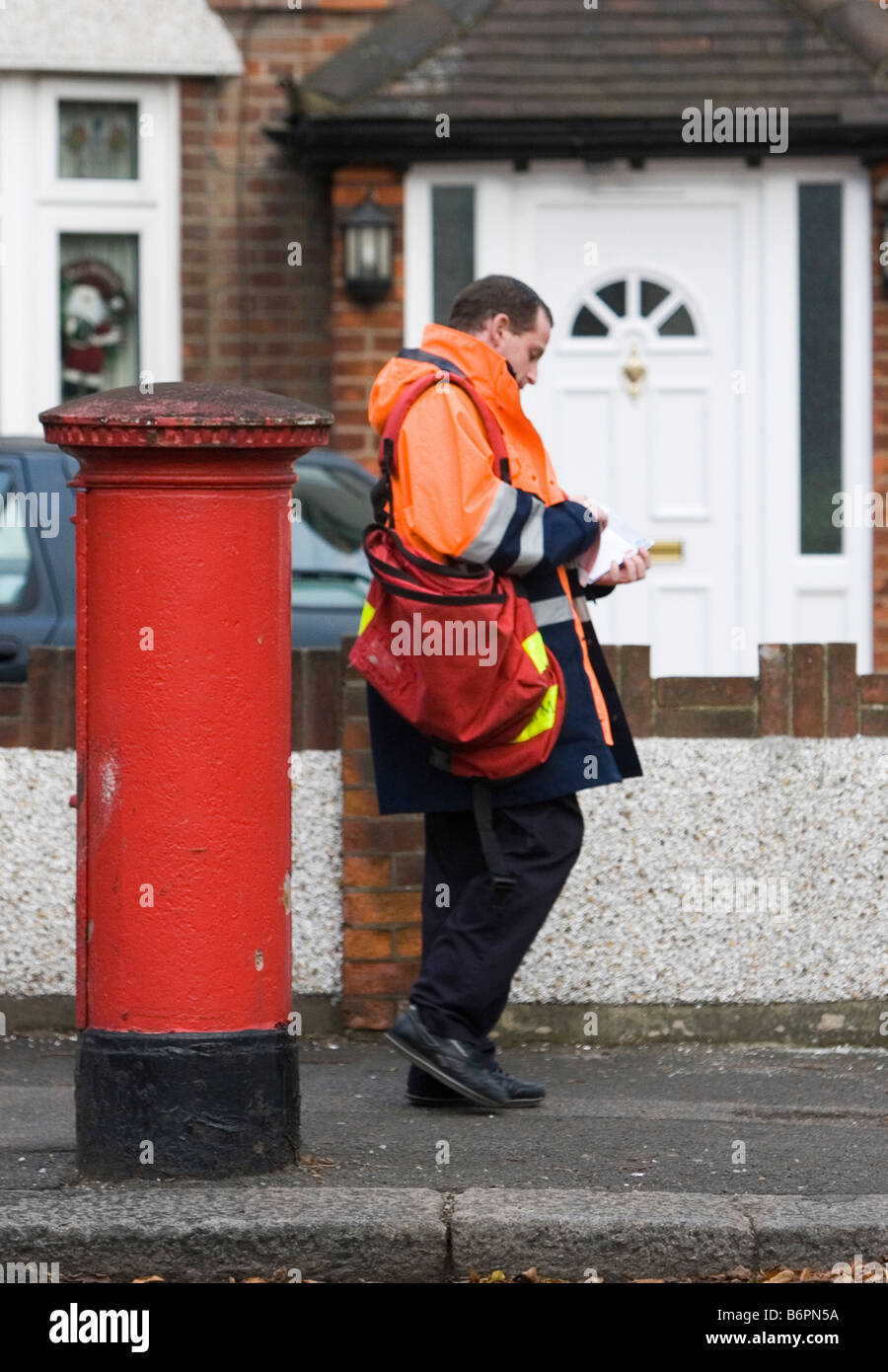 A Royal Mail Postman Walks Along A Road To Deliver Letters