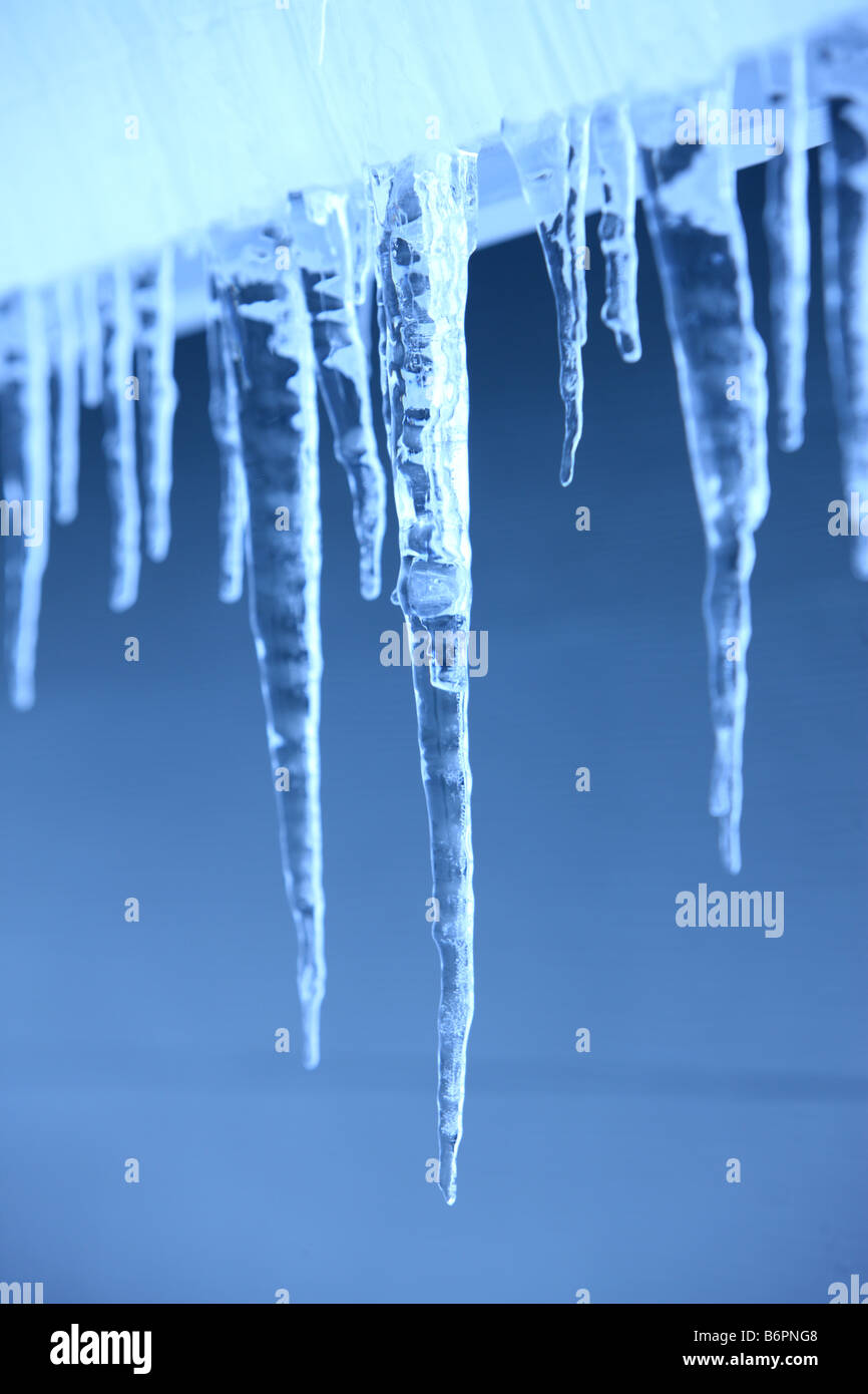 Selective focus Icicles hanging on home exterior - Stock Image