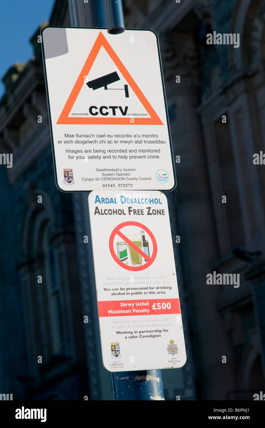 bilingual welsh english language CCTV and Alcohol Free zones signs Aberystwyth town centre Wales UK - Stock Image