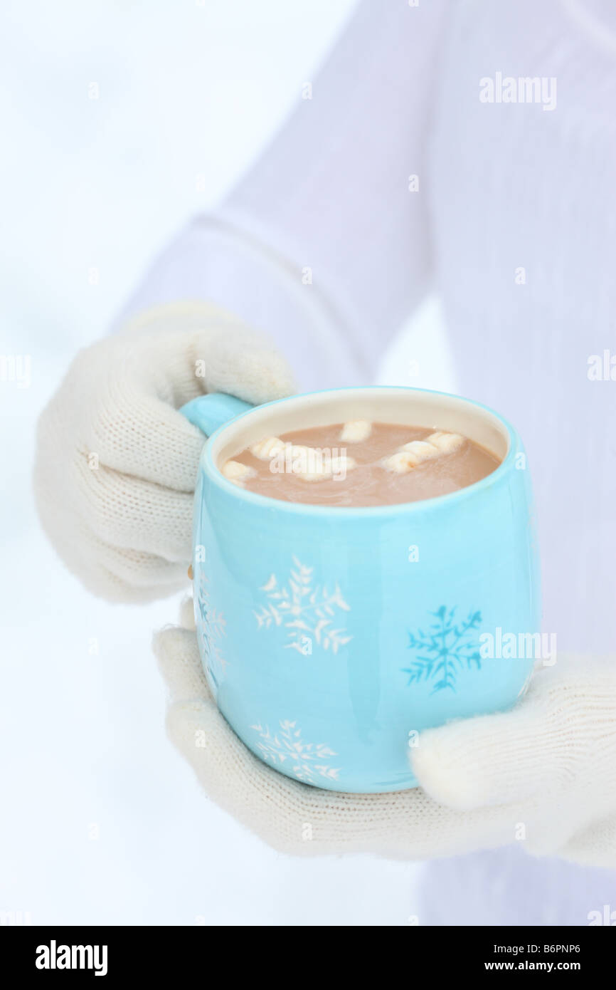 Hands with winter gloves holding blue snowflake mug with hot cocoa and marshmallows - Stock Image