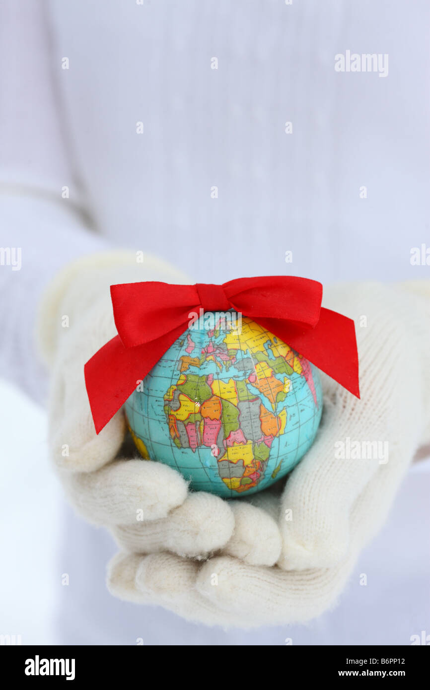 Hands with winter gloves holding Earth with Christmas bow - Stock Image