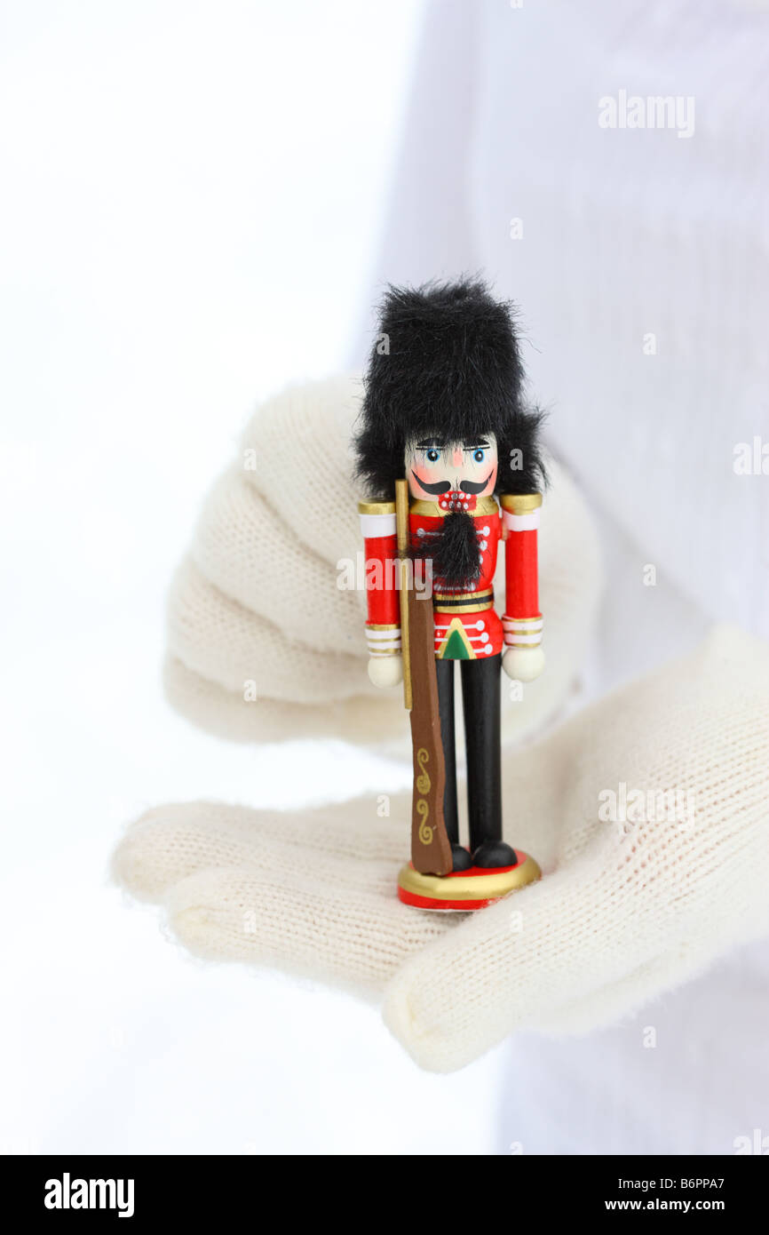 Hands with winter gloves holding Christmas Nutcracker - Stock Image