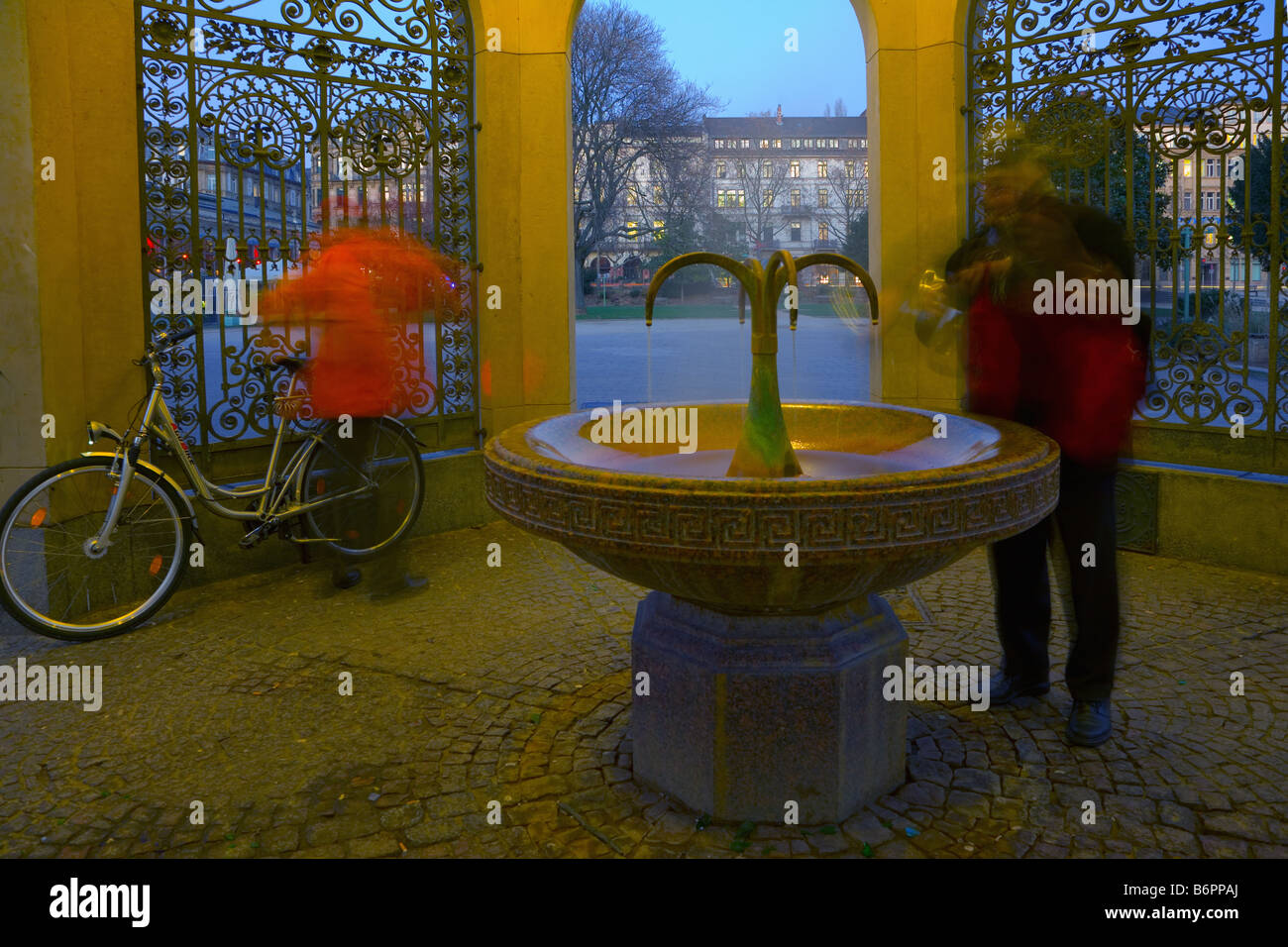 Two men at the Kochbrunnen public fountain, a natural warm mineral spring known for its therapeutic properties - Stock Image