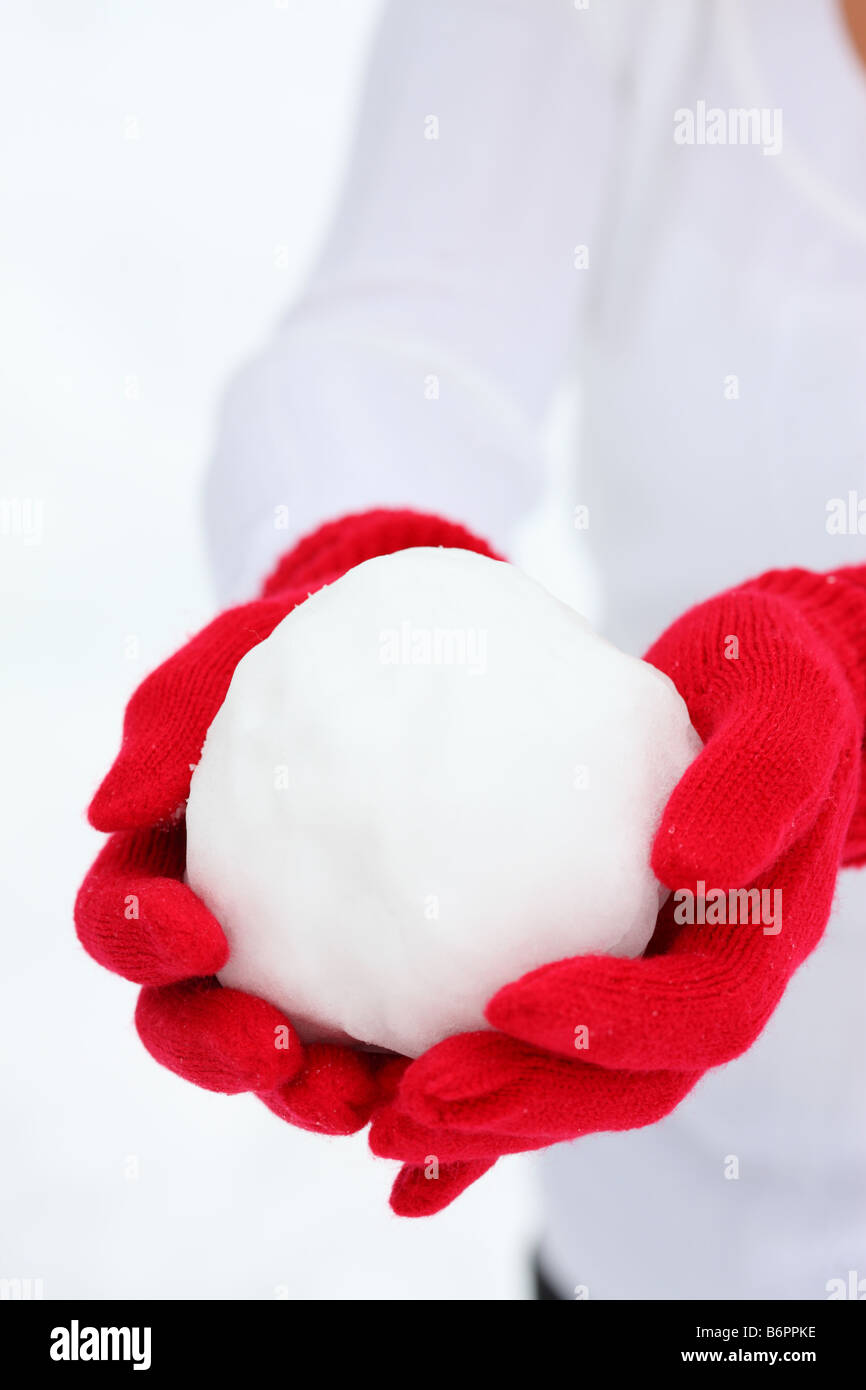 Hands with winter gloves holding Snowball - Stock Image
