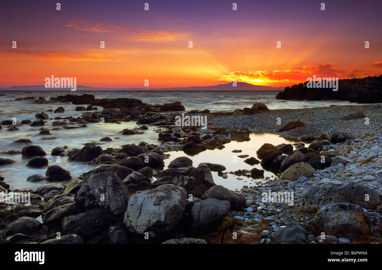 Glorious sunset over rocky sea - Stock Image
