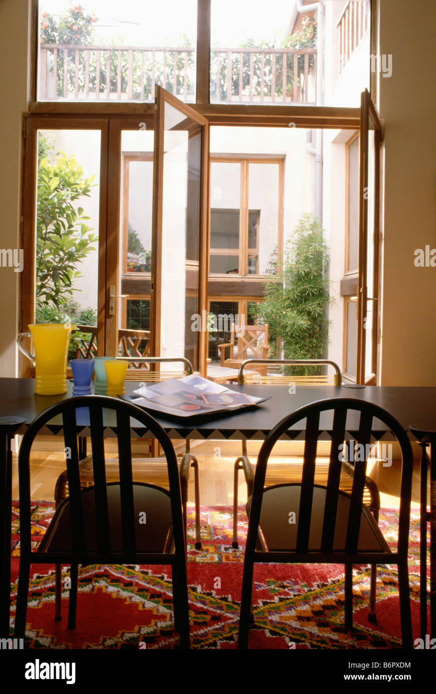 Modern Dining Room With Black Table And Chairs In Front Of French Doors On  To Small Courtyard Garden