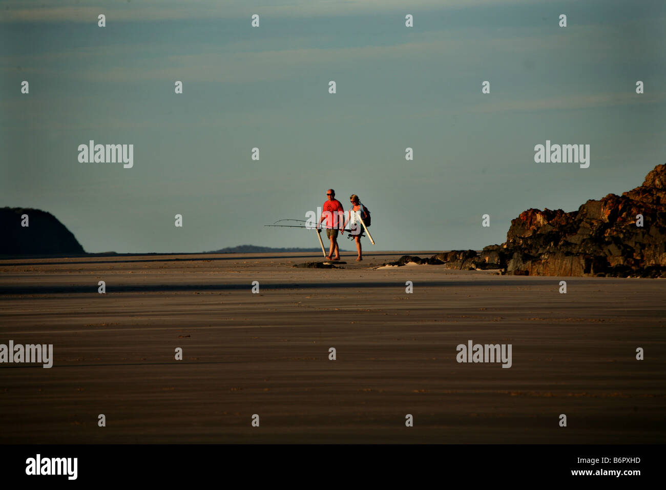 A couple with surf casting rods walk the beach near Delicate Nobby Crescent Heads Australia - Stock Image