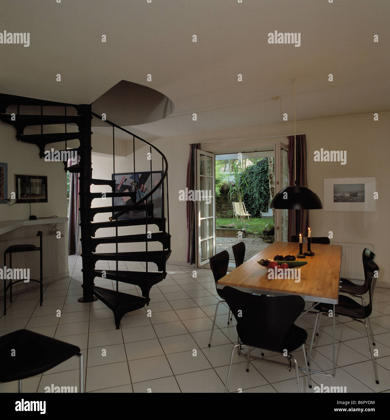 Black Spiral Staircase In Modern White Hall Dining Room With Tiled Floor And Double French Doors Open To Garden