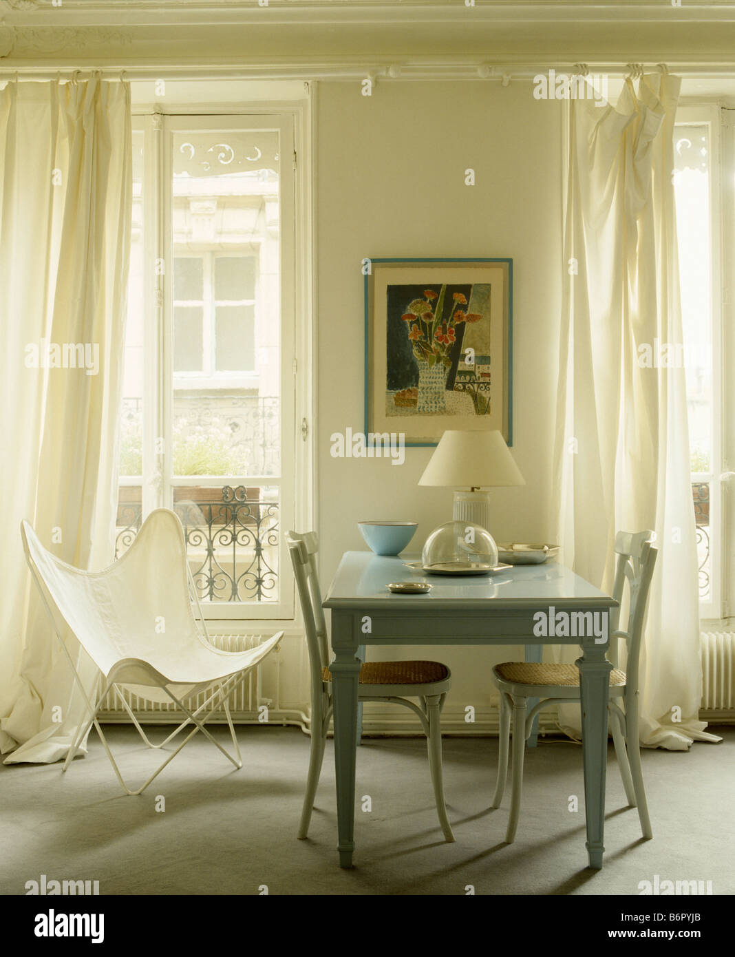White Canvas Butterfly Chair And Pale Blue Table In Dining Room With Cream  Curtains At Tall Windows