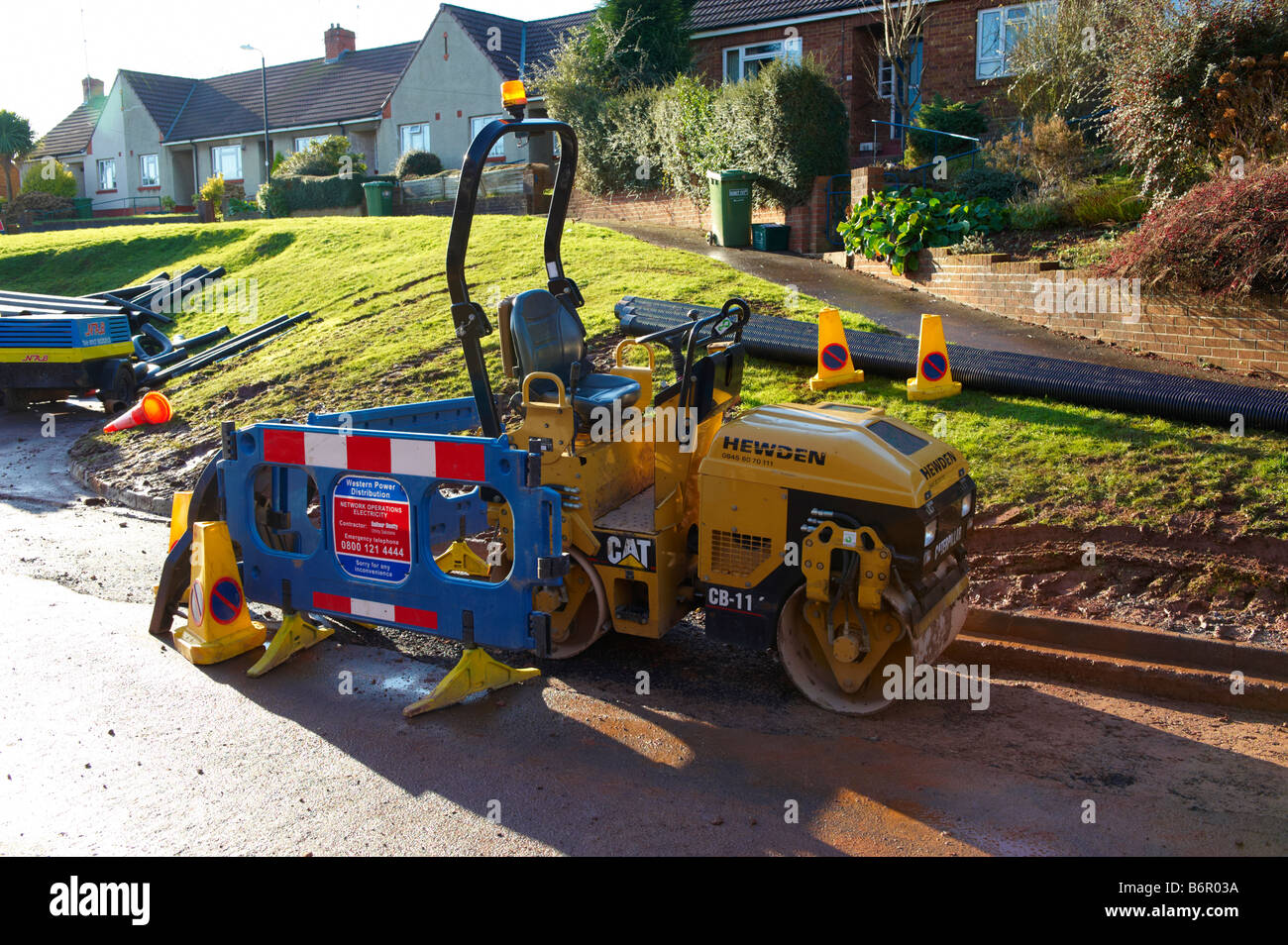 Road roller in road after laying electrical cabling - Stock Image