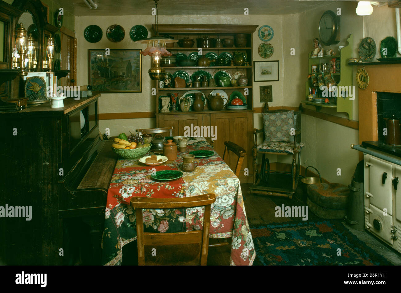 Piano and table with floral cloth in dark oldfashioned kitchen