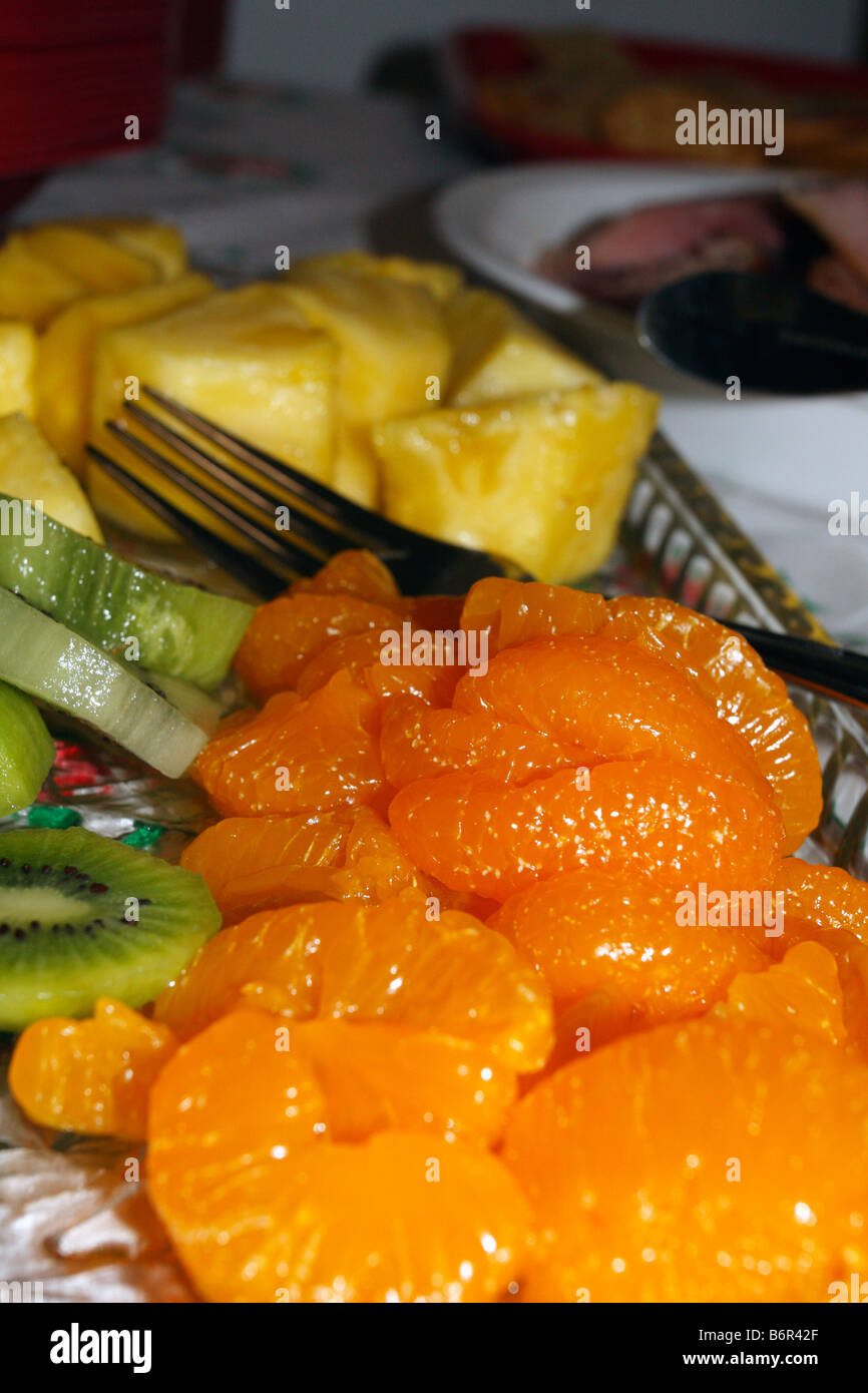 Cut fruit laid out on platter with mandarin oranges, kiwi fruits, fork midground, and pineapple. - Stock Image
