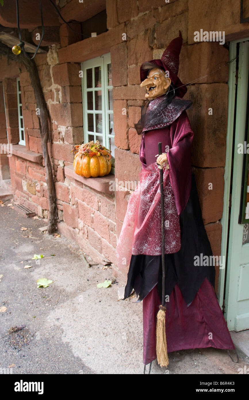 Witch outside shop with pointed hat and snarl + crocked nose  red purple dress full length Vertical  87611_Halloween - Stock Image