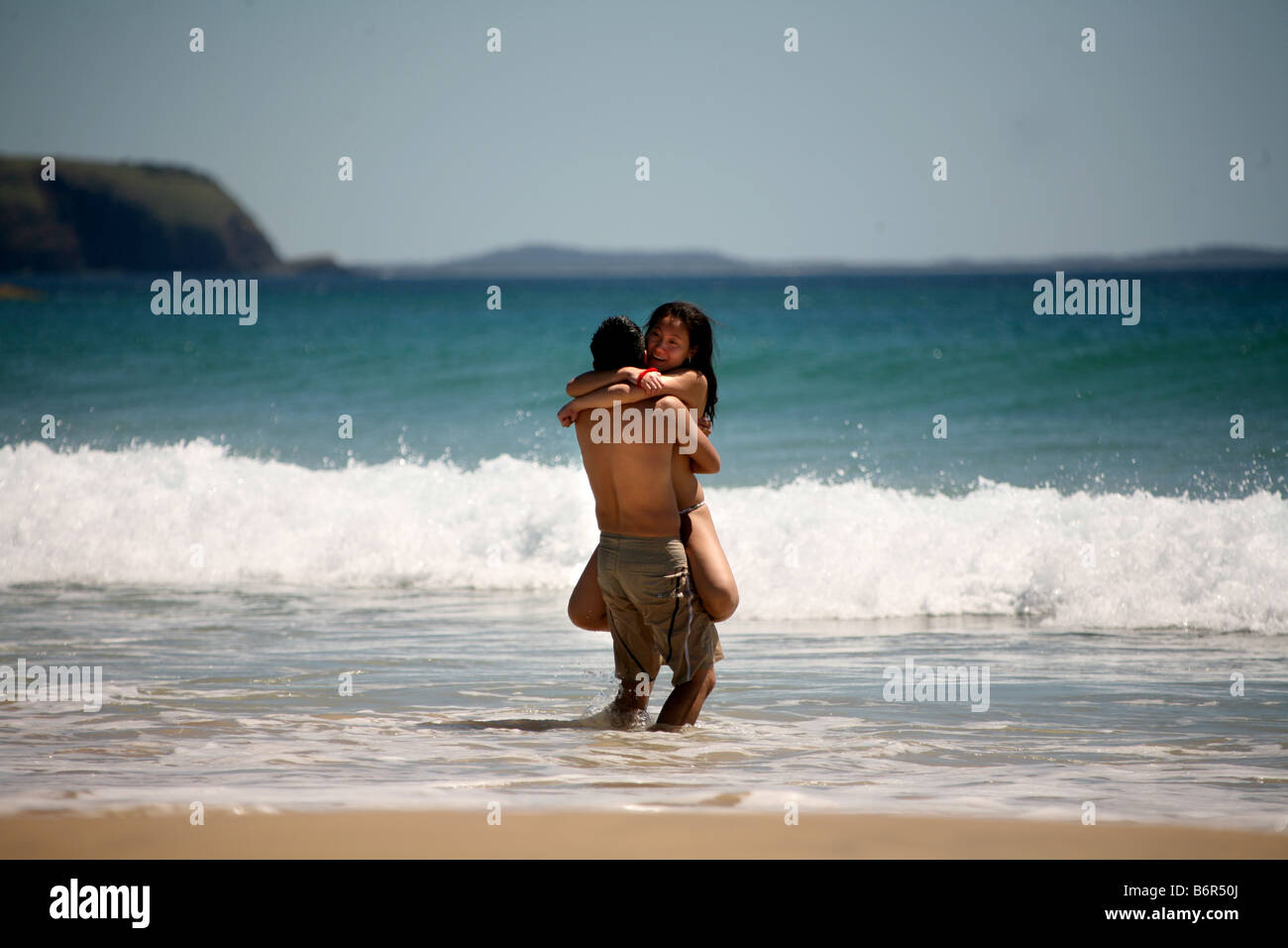 A young Japanese couple embrace as they enjoy perfect day in the surf at Delicate Nobby beach near Crescent heads - Stock Image