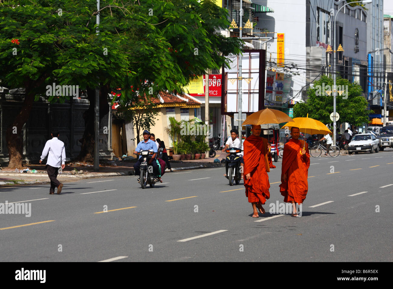 Two (2) buddhist monks in saffron robes walking with umbrellas in the streets of Phnom Penh, Cambodia - Stock Image