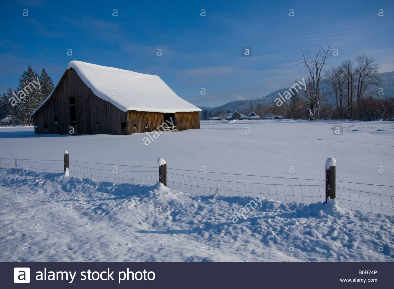 A winter landscape with barn and fence in snowy meadow Stock Photo