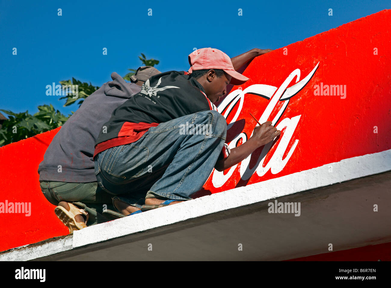 Coca Cola logotype being painted on facade in Antsirabe Antananarivo Madagascar Coca Cola Schriftzug wird auf Fassade - Stock Image