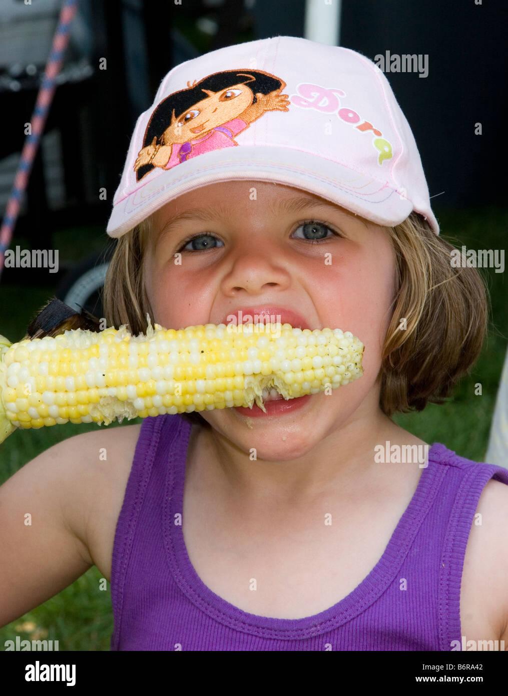 Young girl eats corn on the cob - Stock Image