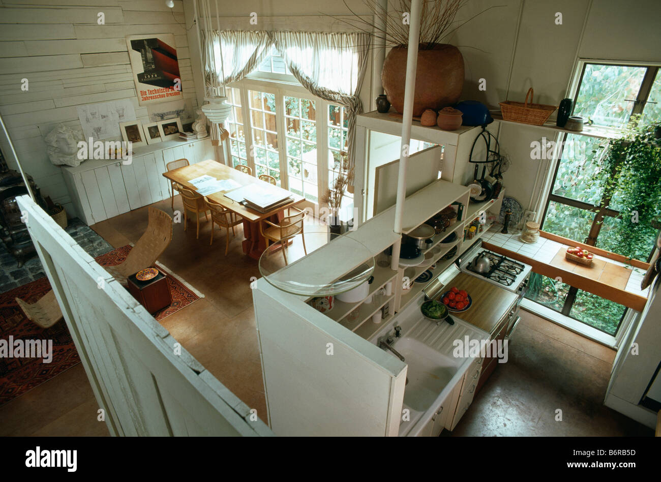 Birdseye view of kitchen and dining room divided by shelf unit in