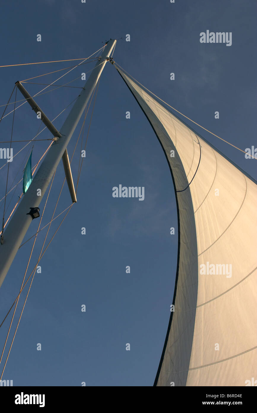 mast and cream white sail with rigging and a blue sky background - Stock Image