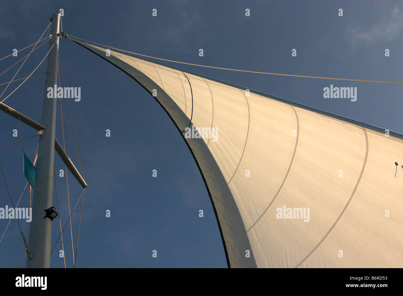 mast with cream white sail with rigging and a blue sky background - Stock Image