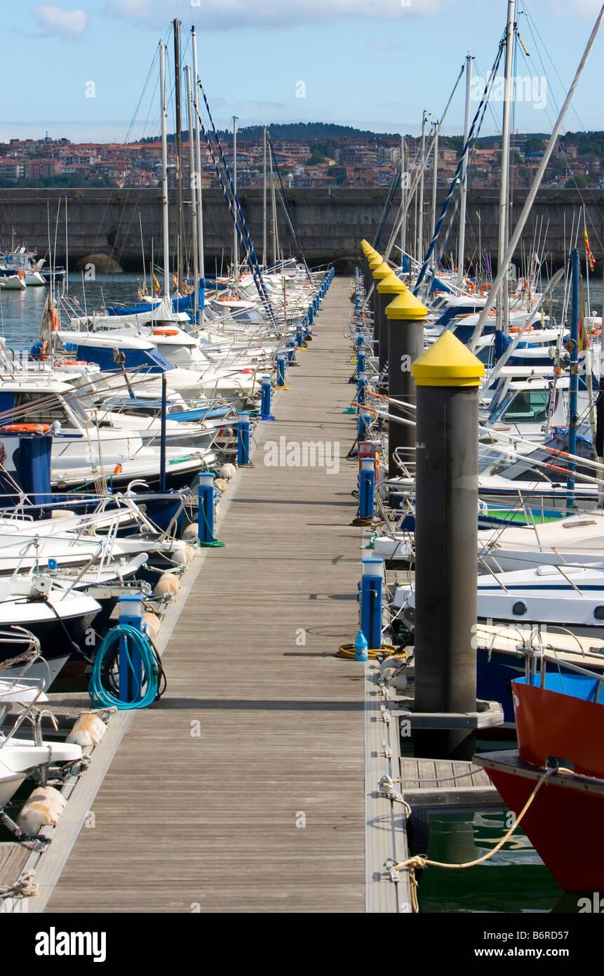 boat resting in paceful water in the dock harbor of Santurce near Bilbao - Stock Image