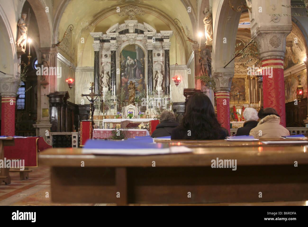 Four women in Catholic church in Venice, Italy - Stock Image