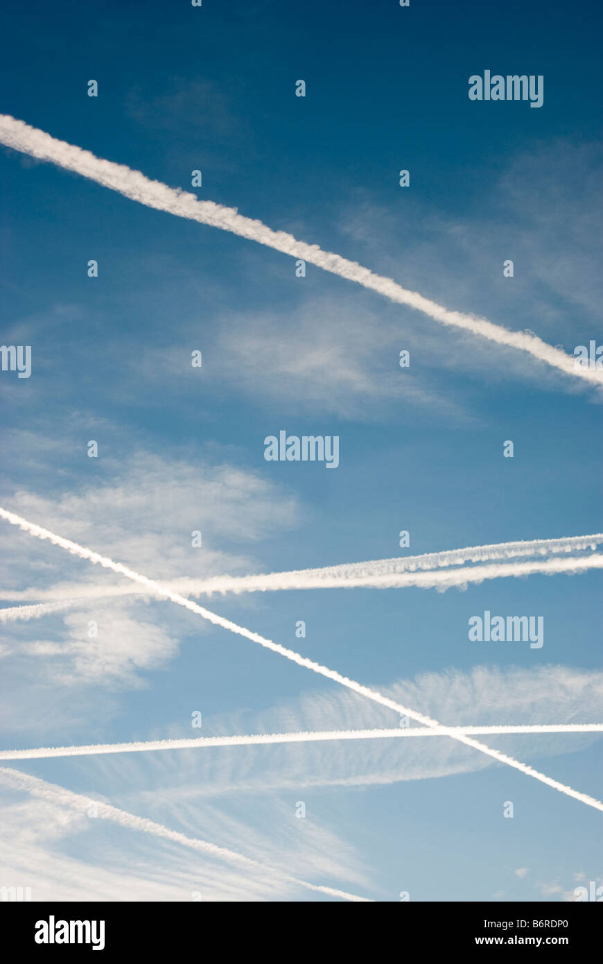 Condensation trails from commercial aircraft flights in a blue sky. - Stock Image