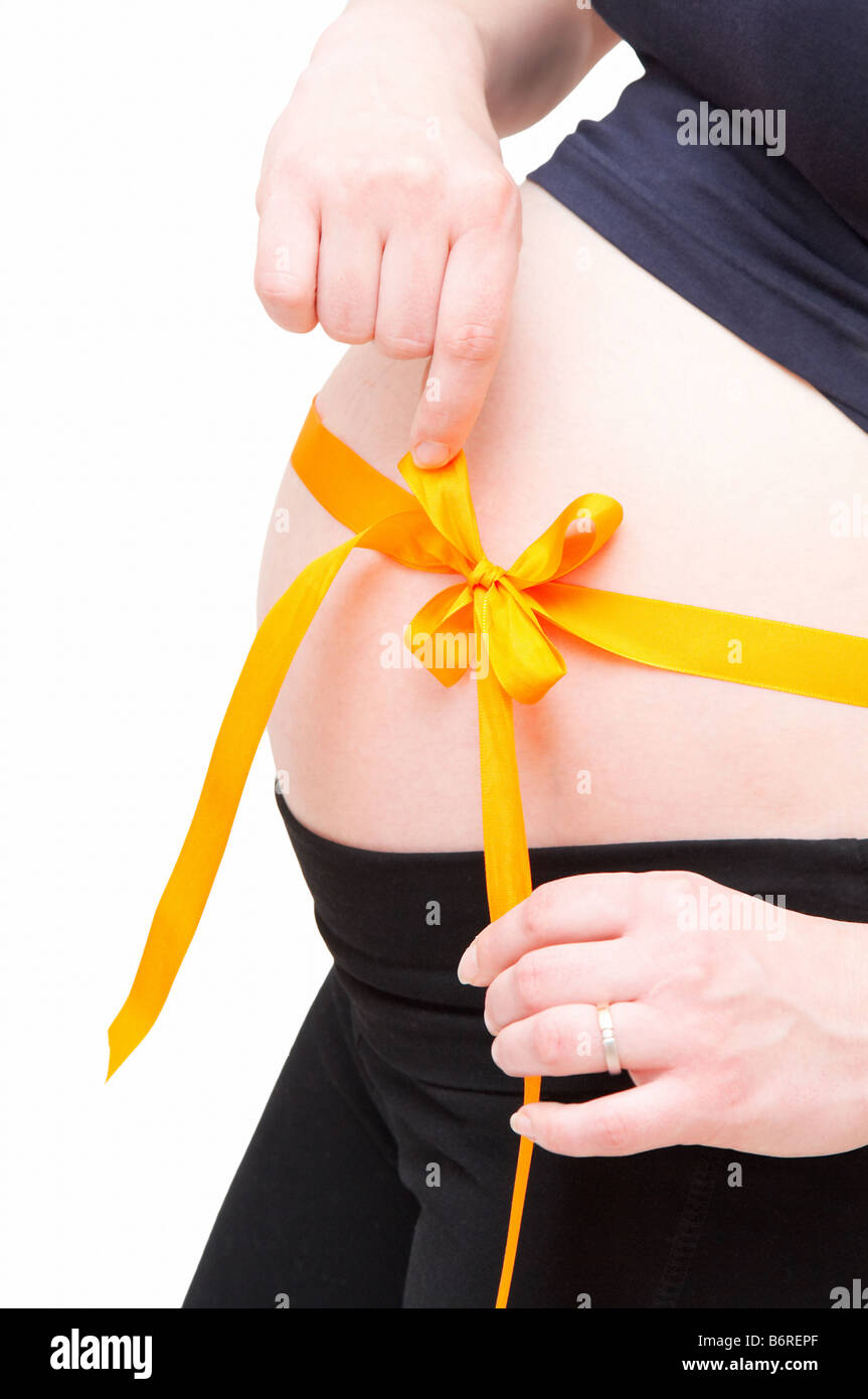 pregnant woman with orange bow - Stock Image