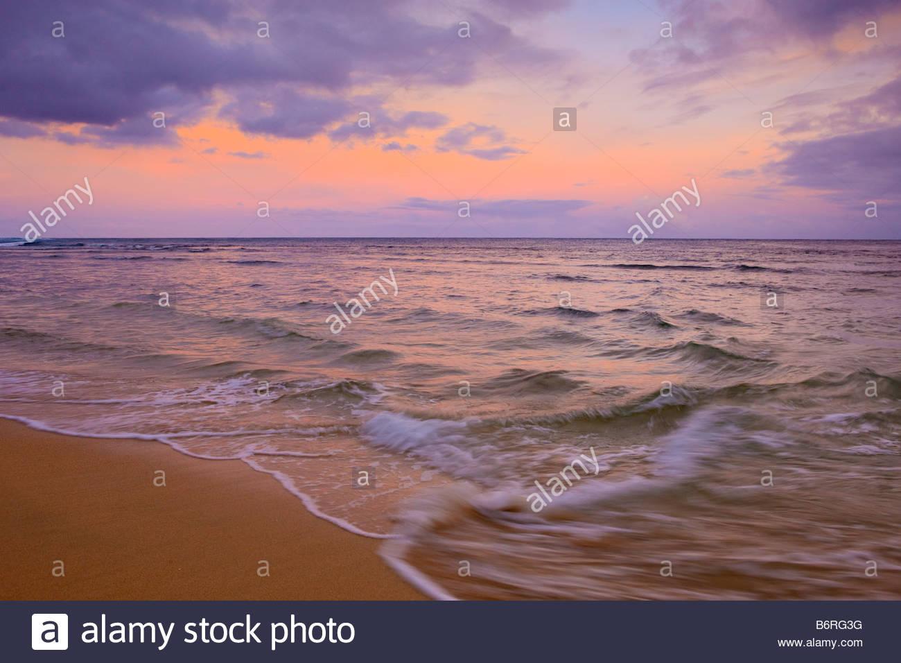 Choppy waves strike Ke'E Beach during a stormy sunrise on the north coast of Kauai, Hawaii. - Stock Image