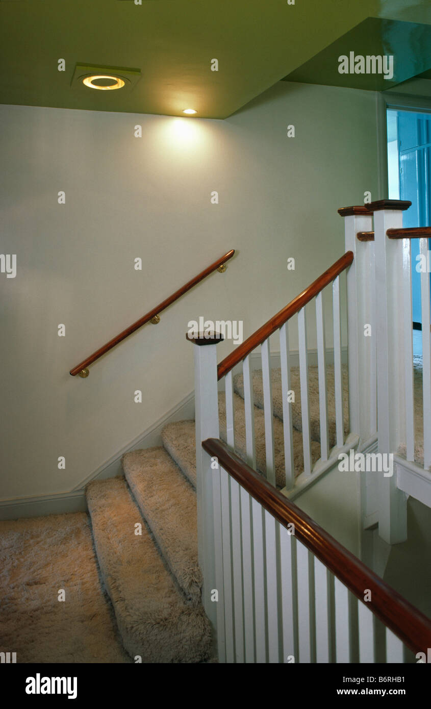 Beige shag-pile carpet on staircase with white banisters and handrail on wall below spotlights - Stock Image
