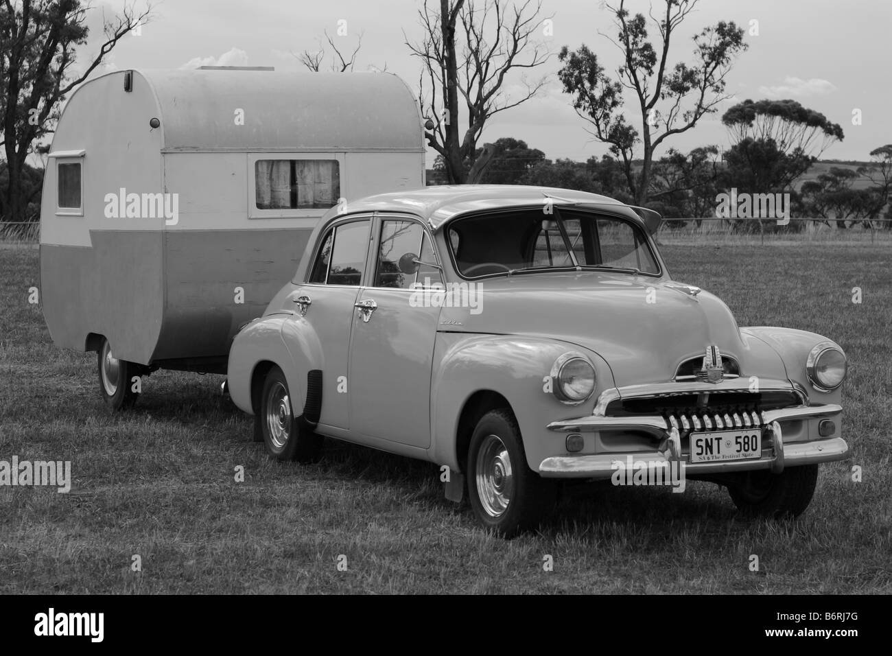 old car and old caravan connected together in a field in south Australia, Australia - Stock Image