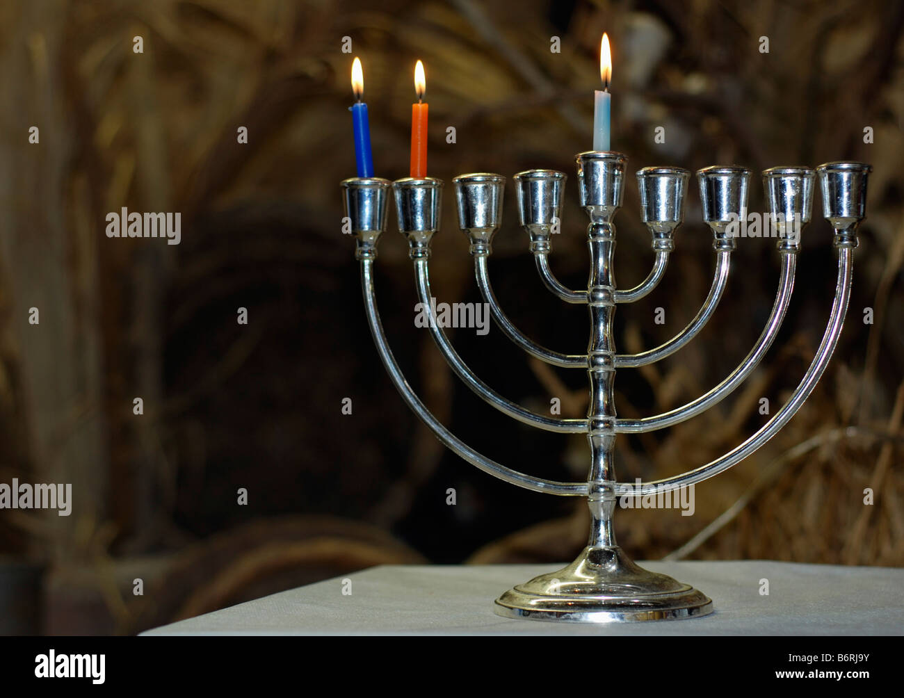 A Chanukia the main symbol of Chanukah The Jewish festival of light with 3 lit candles for the second day - Stock Image
