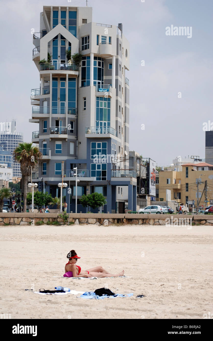 Israel Tel Aviv a woman sunbathing on the beach a modern building on Trumpeldor street in the background - Stock Image
