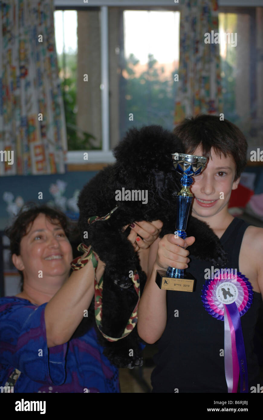 Israel International Dog Show May 17 2008 Proud mother looking at her son a young winner with his dog and trophies - Stock Image