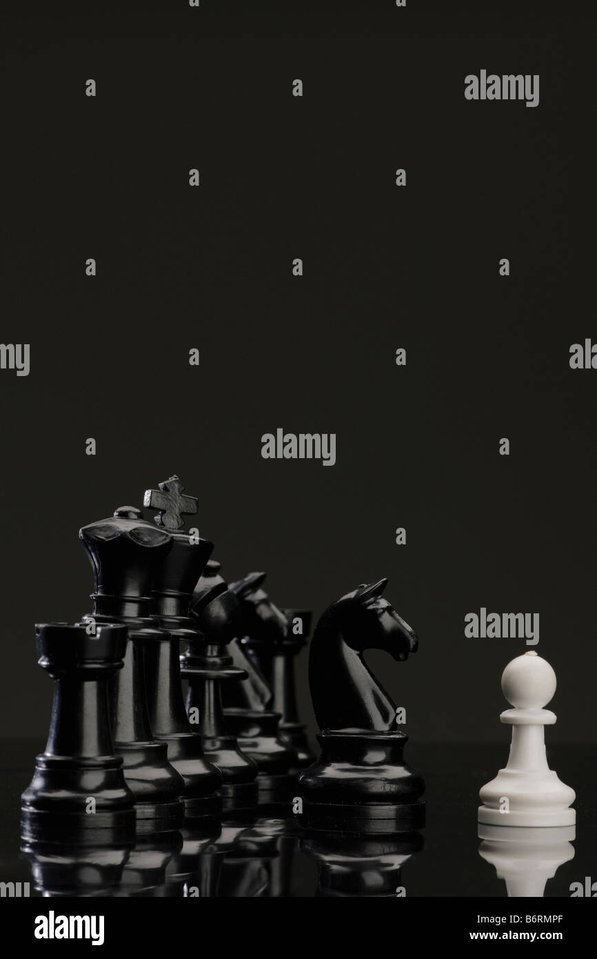 white pawn facing stronger enemy - Stock Image