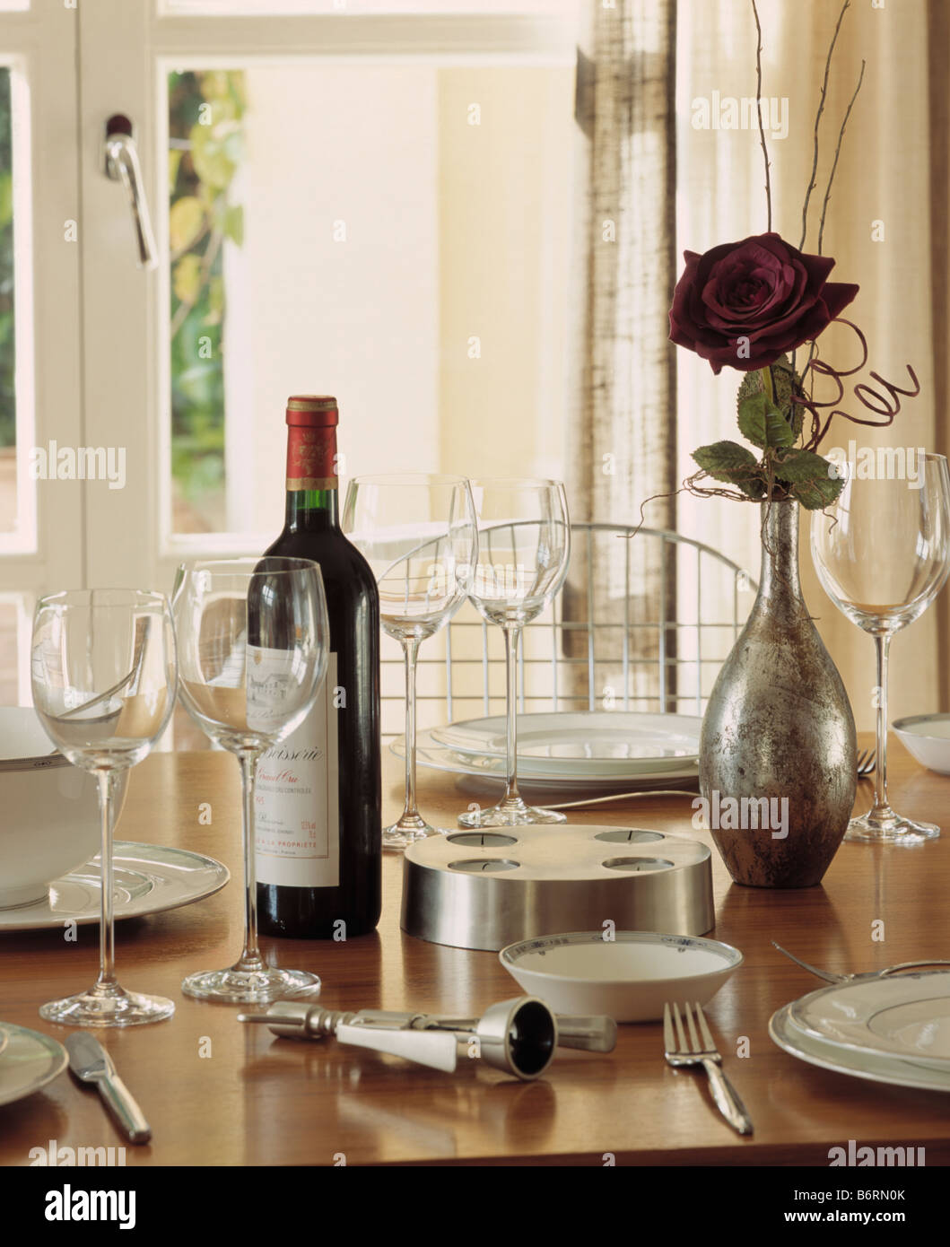 dining place settings. Close-up Of Wine Bottle And Glasses With Place Setting On Dining Table Red Rose In Metal Vase Settings