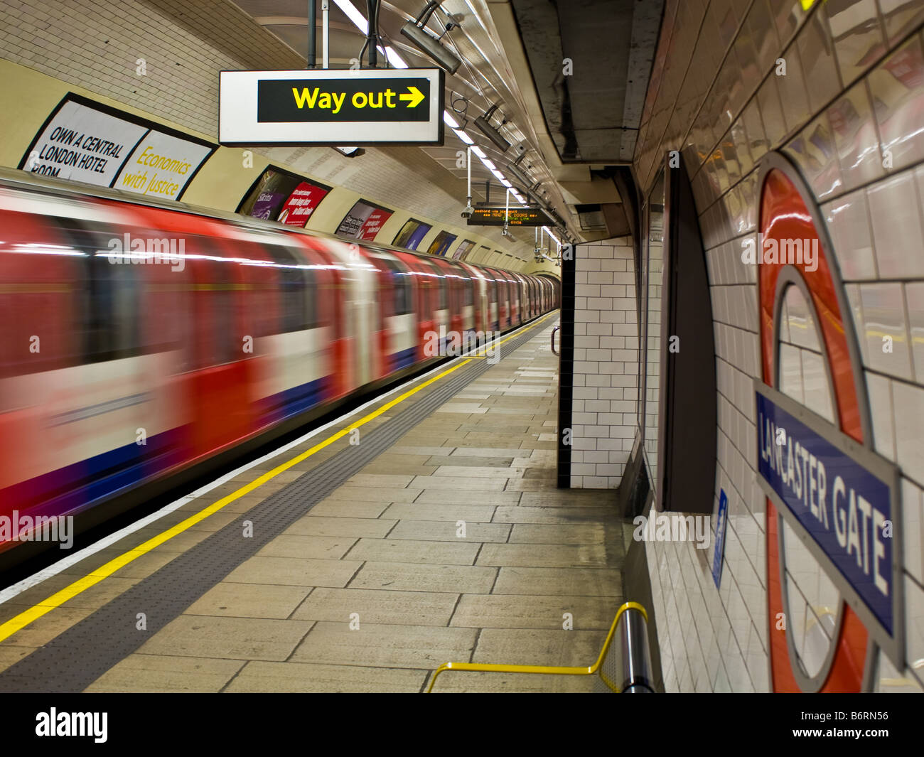 A tube train departs Lancaster Gate station on the London Underground - Stock Image
