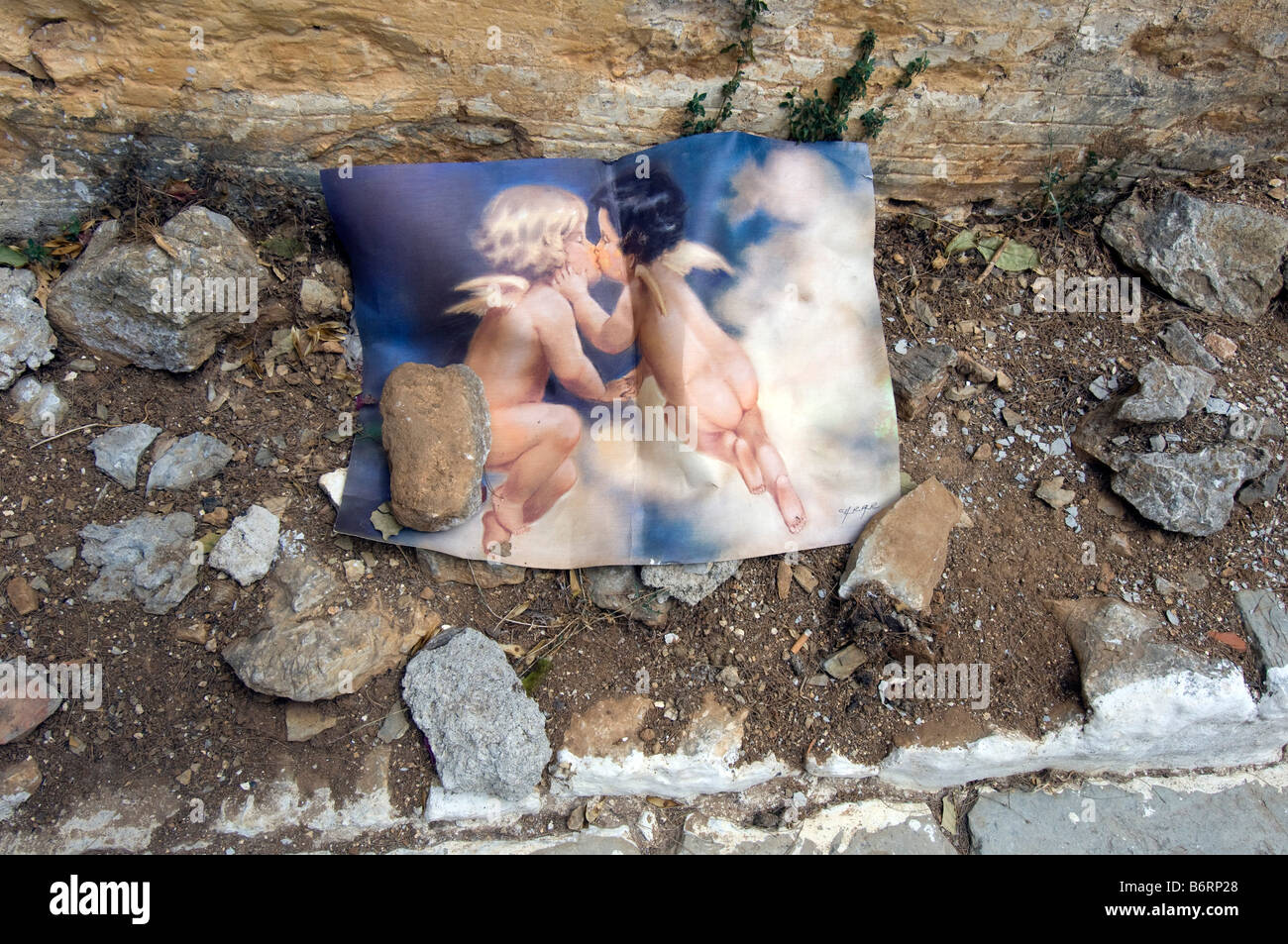 A discarded picture of two cherubs kissing - Stock Image