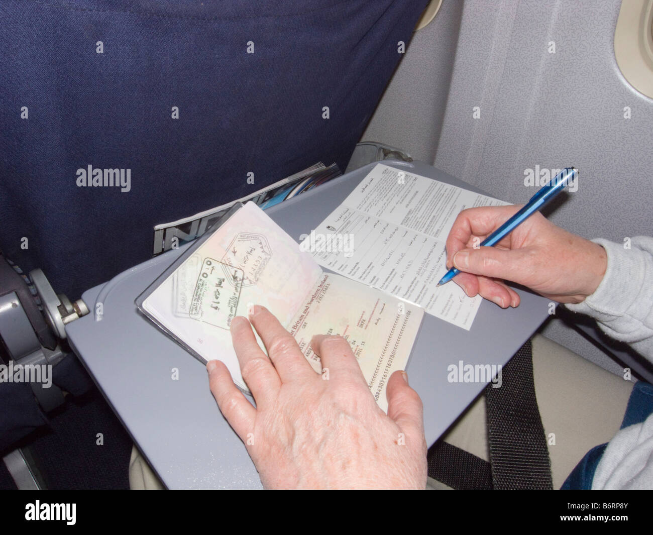 Person filling in Embarkation form with passport details on aeroplane seat table for entry into Morocco from UK - Stock Image