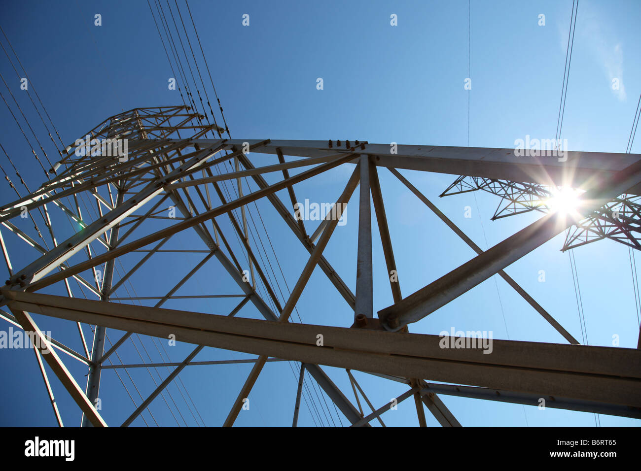 power lines with sun shining and blue sky - Stock Image
