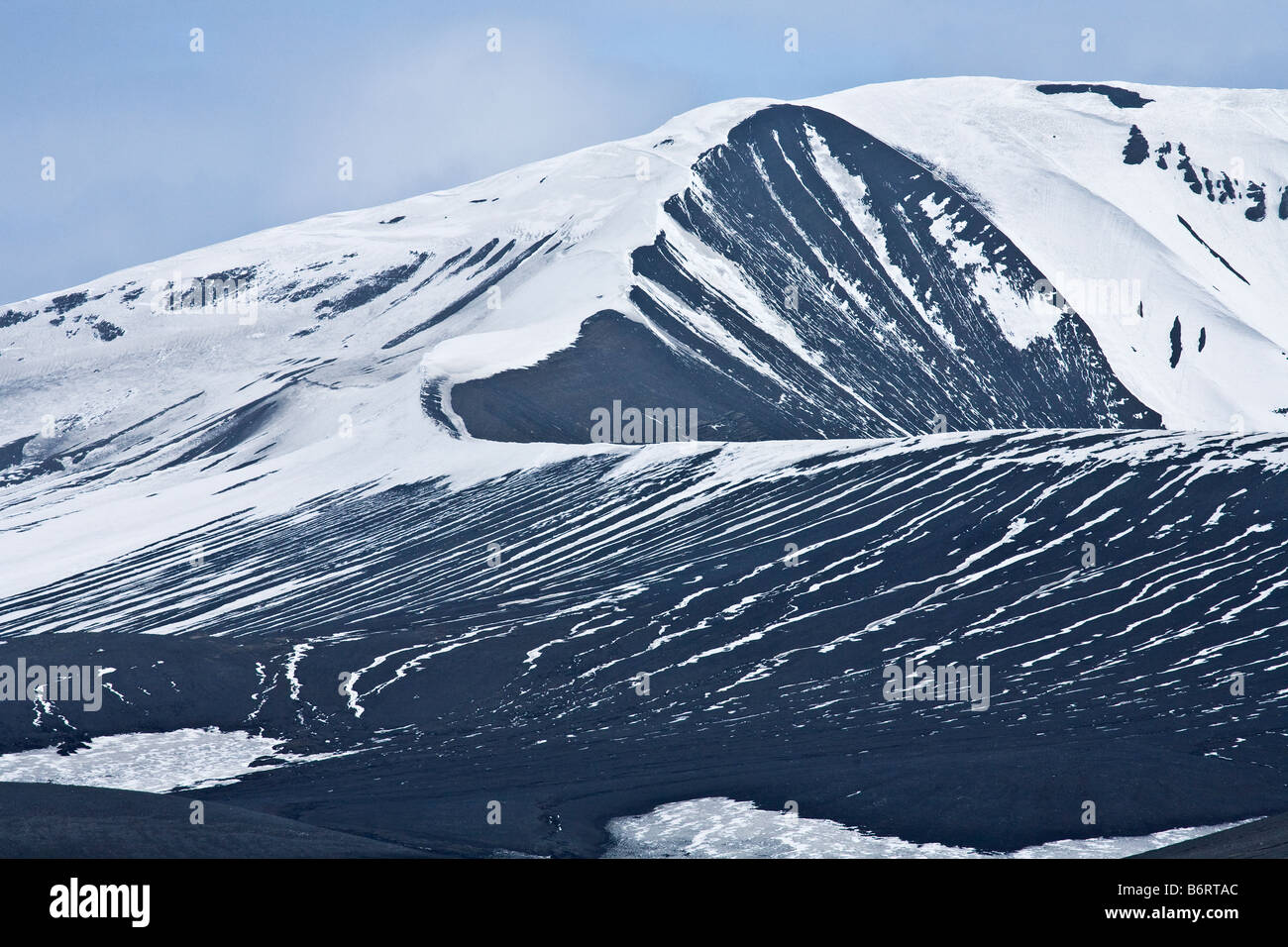 Volcanic rocks and ash mix with glacial ice on shores of Deception Island Antarctica - Stock Image