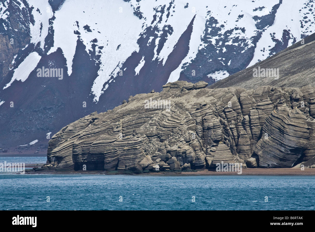 Solidified lava volcanic rocks and ash mix with glacial ice on shores of Deception Island Antarctica - Stock Image