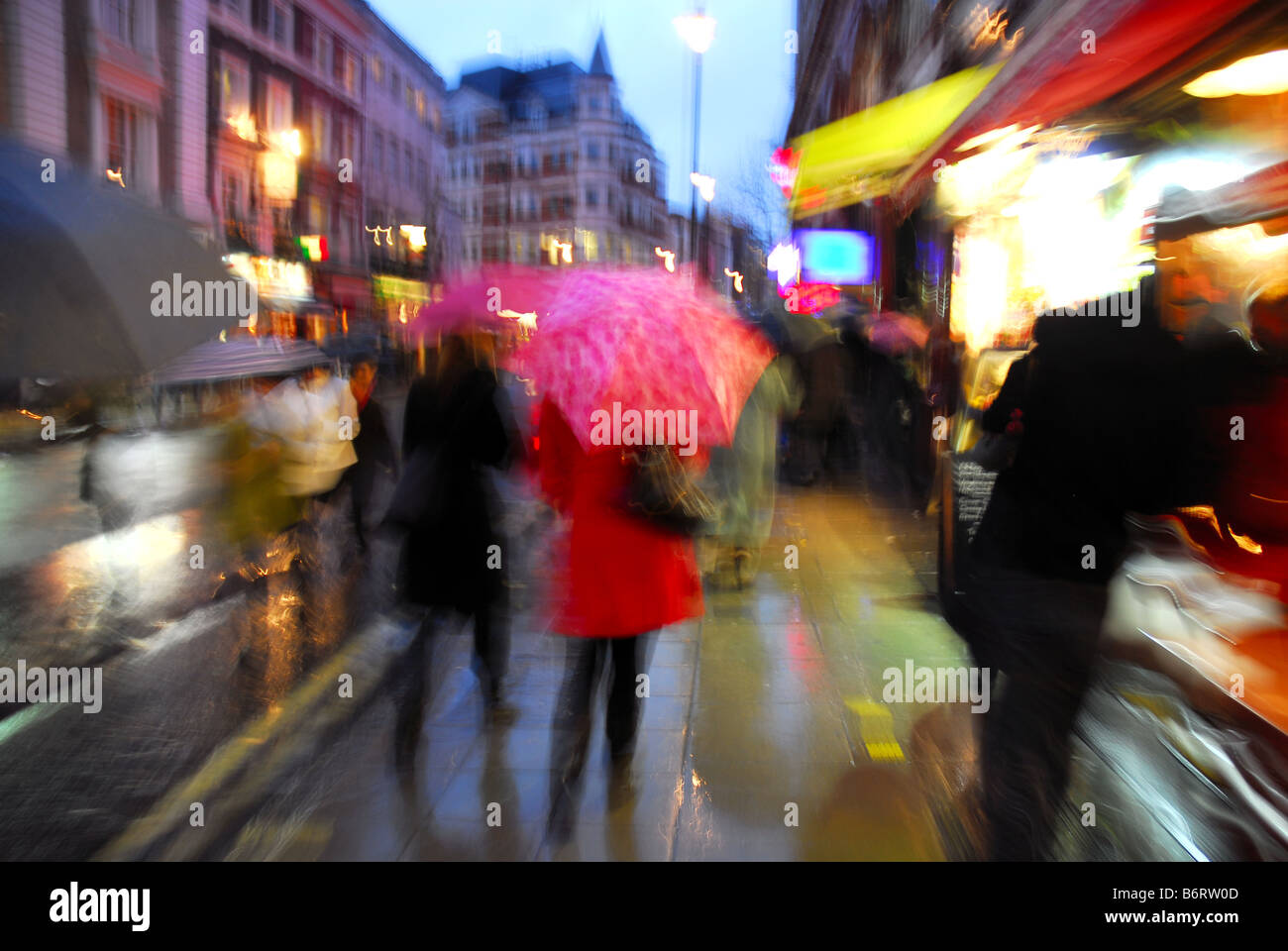 Rainy London street with shoppers and umbrellas - Stock Image